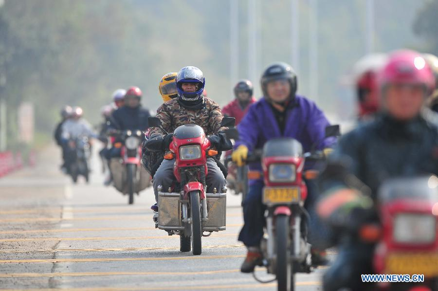 Migrant workers ride motorbikes on their way back home on the 321 National Highway in Wuzhou, south China's Guangxi Zhuang Autonomous Region, Jan. 29, 2013. Many Guangxi migrant workers working in south China's Guangdong Province got around the ticket buying predicament during the Spring Festival travel rush which lasts for forty days by riding back home thanks to the well-developed roads connecting Guangxi and Guangdong. (Xinhua/Huang Xiaobang)