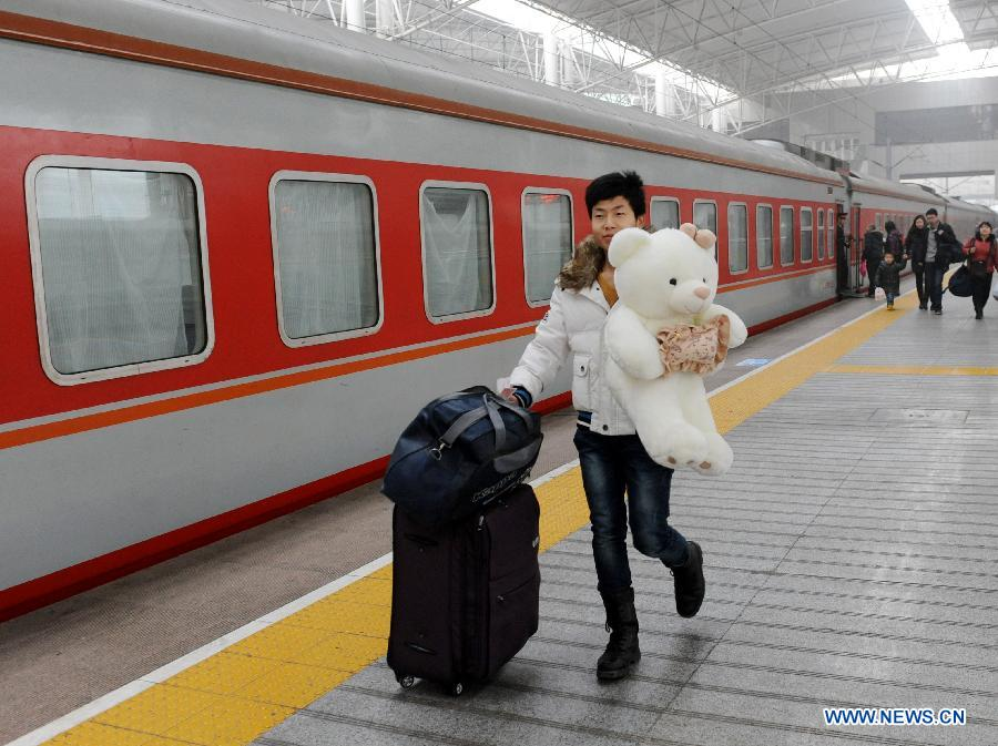 A passenger holding a gift for his friend prepares to board the train at the Zhengzhou Railway Station in Zhengzhou, capital of central China's Henan Province, Jan. 30, 2013. The 40-day Spring Festival travel rush started on Jan. 26. The Spring Festival, which falls on Feb. 10 this year, is traditionally the most important holiday of the Chinese people. It is a custom for families to reunite in the holiday, a factor that has led to massive seasonal travel rushes in recent years as more Chinese leave their hometowns to seek work elsewhere. Public transportation is expected to accommodate about 3.41 billion travelers nationwide during the holiday, including 225 million railway passengers.(Xinhua/Li Bo)
