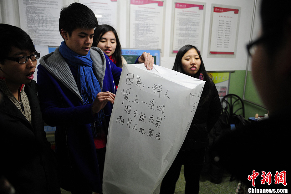Exchange students write a poem on a handmade lantern where they wish that the friendship between the students across-strait will last forever. (Chinanews/Cui Nan)