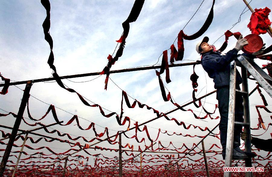 A young man hangs chains of firecrackers on a bank of the Yellow River in Zhengzhou, capital of central China's Henan Province, Feb. 3, 2005. The crackling and spluttering sound from firecrackers during the Spring Festival or Chinese Lunar New Year is expected to intimidate the Nian, a beast in Chinese mythology which comes out of hiding to attack people around Chinese New Year. Chinese people who live in the central China region have formed various traditions to celebrate the Chinese Lunar New Year. (Xinhua/Wang Song)