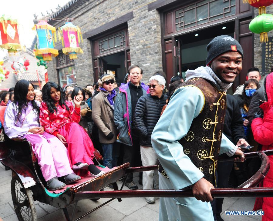 A foreign student carries his friends forward with a rickshaw during their visit to Zhoucun District of Zibo City, east China's Shandong Province, Feb. 10, 2013. Over 20 foreign students from different countries came to the ancient town on Sunday to celebrate the Spring Festival with local people. The Spring Festival falls on Feb. 10 this year. (Xinhua/Dong Naide)