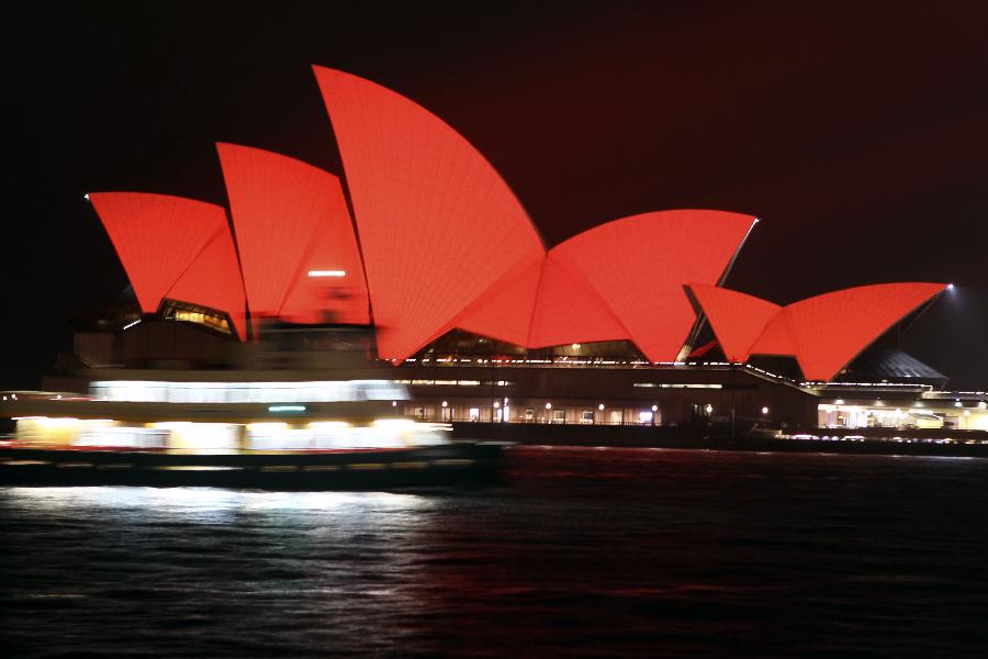 A ferry boat moves in the front of the Sydney Opera House, which is lit up in red to celebrate the Chinese lunar New Year, in Sydney, Australia, on Feb. 10, 2013. The Chinese Spring Festival falls on Feb. 10 this year, marking the start of the Chinese Year of the Snake. (Xinhua/Jin Linpeng)