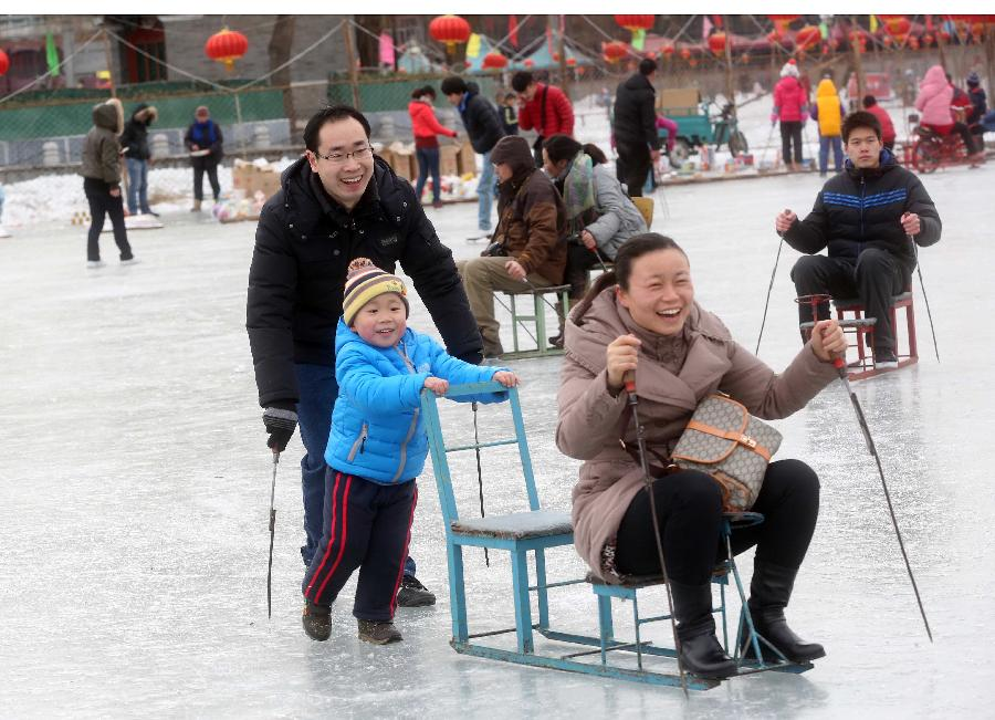 A family plays at the Shichahai Lake Ice Rink on the first day of the Chinese Lunar New Year in Beijing, capital of China, Feb. 10, 2013. Many people here chose to spend the first day of the Chinese Lunar New Year on the ice. (Xinhua/Chen Xiaogen)
