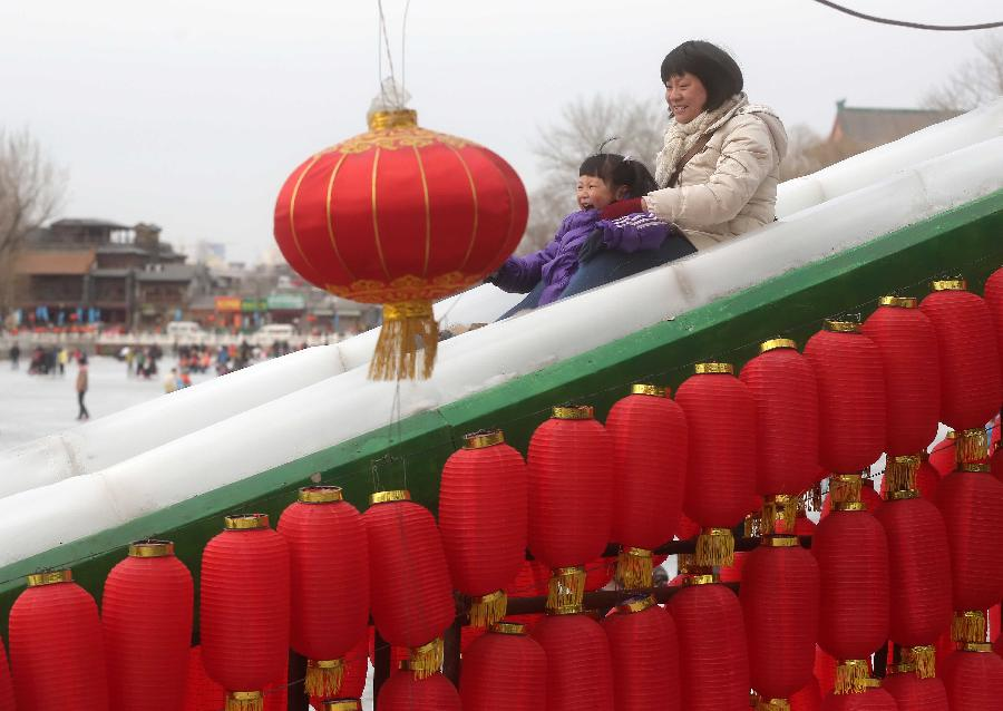 A mother and her daughter play slide at the Shichahai Lake Ice Rink on the first day of the Chinese Lunar New Year in Beijing, capital of China, Feb. 10, 2013. Many people here chose to spend the first day of the Chinese Lunar New Year on the ice. (Xinhua/Chen Xiaogen)