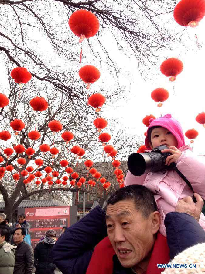 A man carrying his child is seen at a temple fair held to celebrate the Spring Festival, or the Chinese Lunar New Year, in Beijing, capital of China, Feb. 10, 2013. (Xinhua/He Guang)