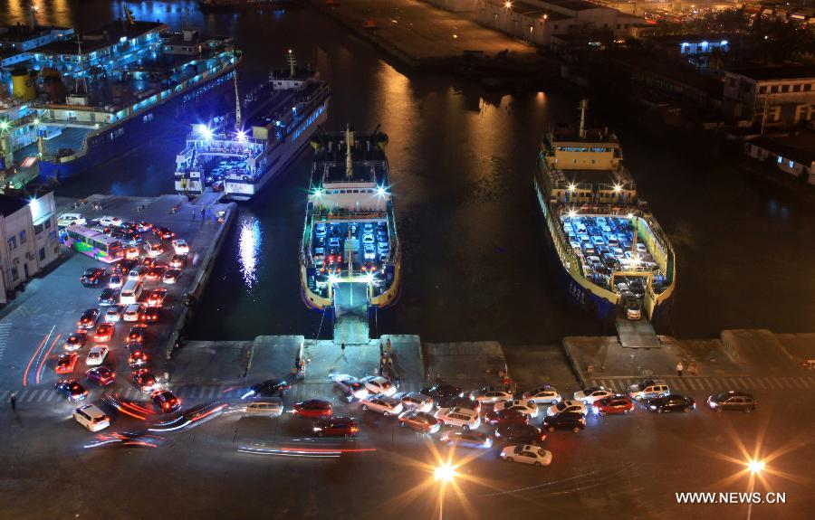 Vehicles which were detained by a heavy fog leave a port in Haikou, capital of south China's Hainan Province, late Feb. 15, 2013. A total of 46,000 passengers and 8,700 vehicles have left the Port of Haikou from 8:00 p.m. Friday to 8:00 a.m. Saturday, after being detained by a heavy fog that disrupted the waterway traffic across the Qiongzhou Strait. (Photo/ Xinhua)