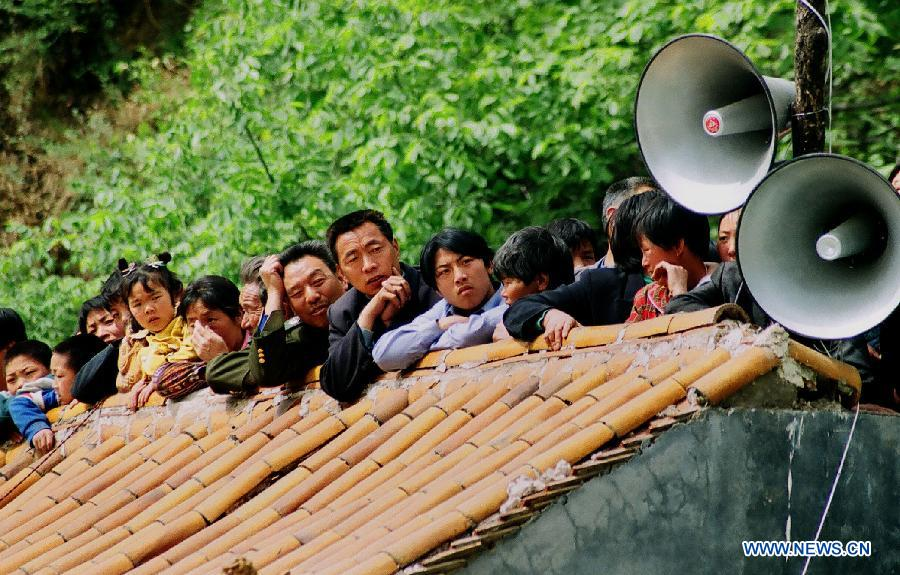 File photo taken on April 27, 2002 shows villagers gathering on a rooftop to watch a Shehuo performance in Wangwu Township of Jiyuan, central China's Henan Province. (Xinhua/Wang Song)