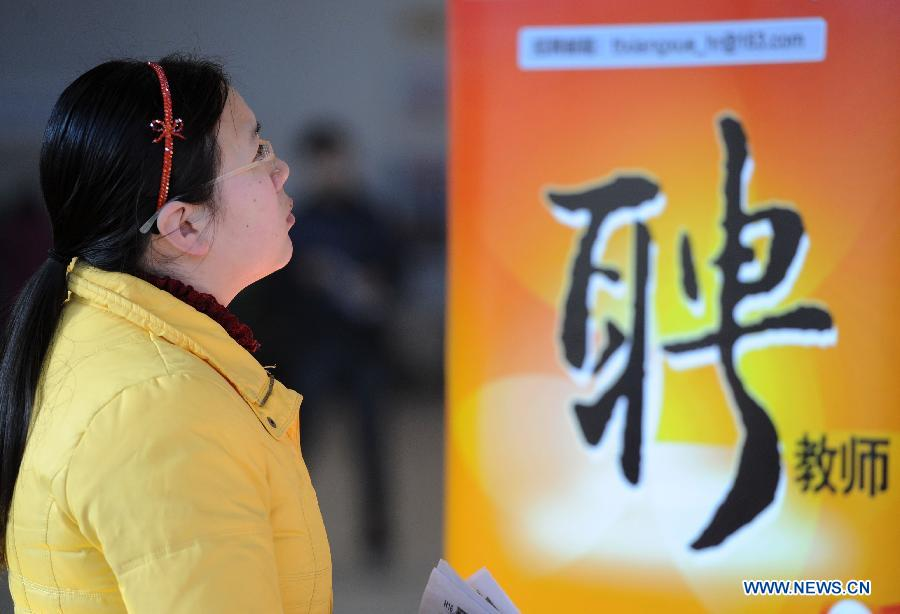 A job seeker reads employment information at a job fair in Beijing, capital of China, Feb. 23, 2013. About 25,000 job opportunities were offered at the job fair. (Xinhua/Luo Xiaoguang)
