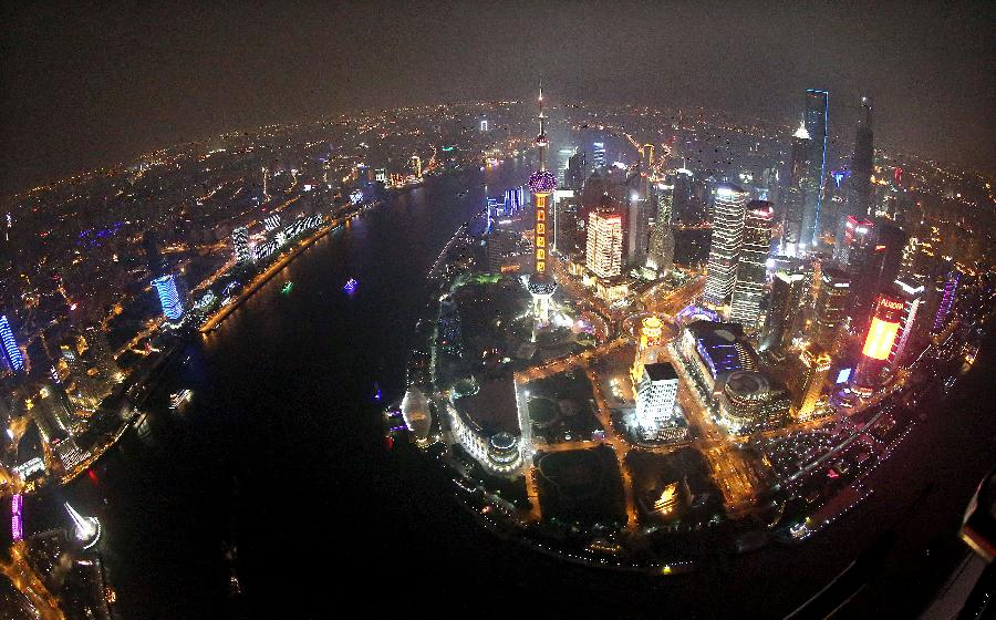 Photo taken on Feb. 24, 2013 shows the aerial view of the illuminated buildings along the banks of the Huangpu River in Shanghai, east China. (Xinhua/Fan Jun)