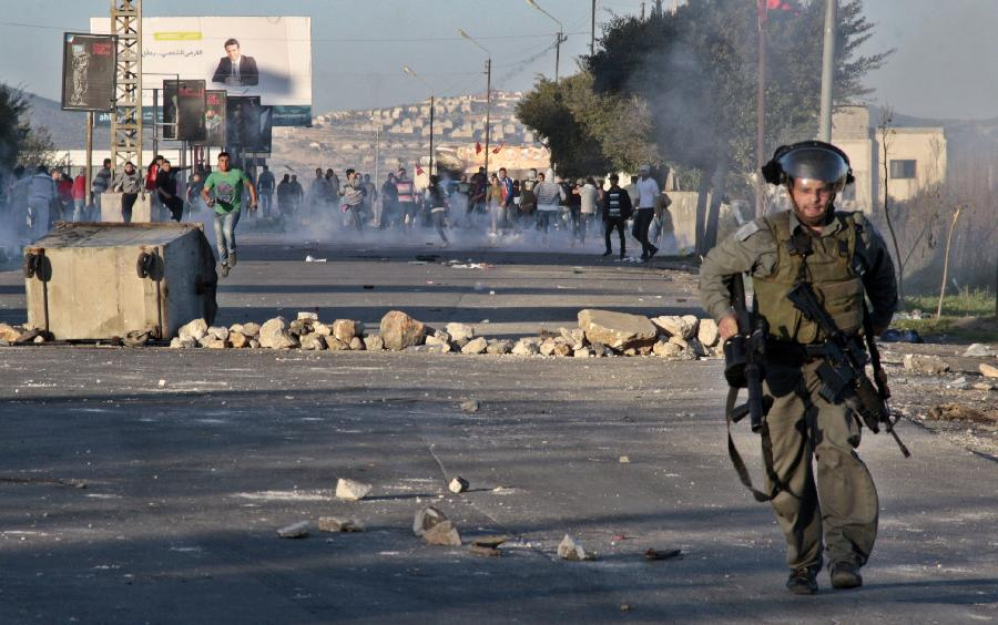 Palestinian protesters throw stones at Israeli soldiers during clashes at Hawara checkpoint near the West Bank city of Nablus on Feb. 24, 2013. (Xinhua/Nidal Eshtayeh)