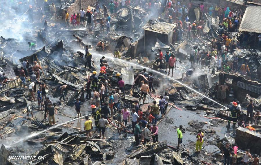 Fire fighters try to extinguish a fire that broke out at a slum at Kalyanpur area in Dhaka, capital of Bangladesh, Feb. 27, 2013. About 150 shanties were destroyed, fire brigade said. (Xinhua/Shariful Islam)