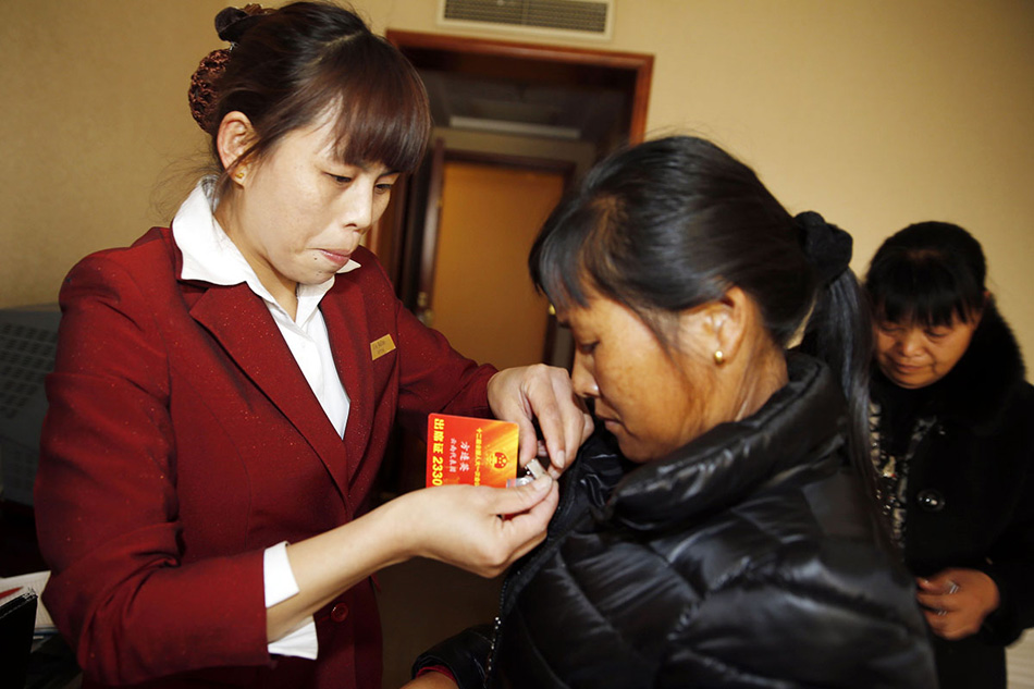 A hotel attendant helps Fang wear the ID card. (People's Daily Online/Ji Yu)