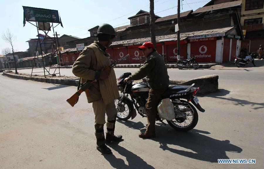 An Indian paramilitary soldier stops a man on motorcycle during curfew in Srinagar, summer capital of Indian-controlled Kashmir, March 6, 2013. Indian army troopers on Tuesday killed a young man and wounded another after opening gunfire at protesters in Indian-controlled Kashmir, officials said. (Xinhua/Javed Dar)