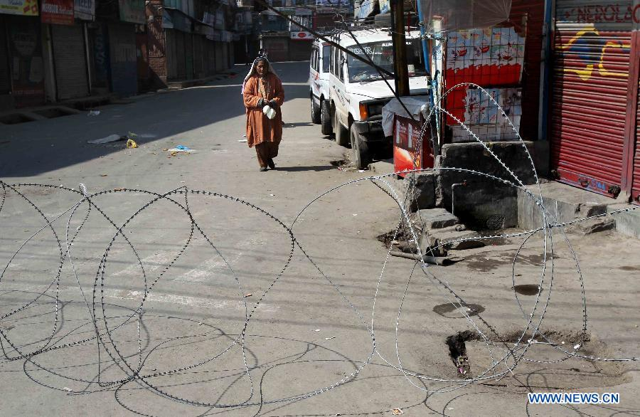 A Kashmiri woman carries milk packets as she walks past a barbed wire during curfew in Srinagar, summer capital of Indian-controlled Kashmir, March 6, 2013. Indian army troopers on Tuesday killed a young man and wounded another after opening gunfire at protesters in Indian-controlled Kashmir, officials said. (Xinhua/Javed Dar)