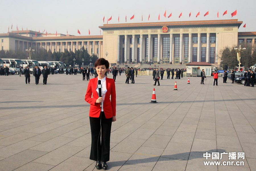 A television host wearing red suit reports at Tiananmen Square. (Photo/www.cnr.cn)