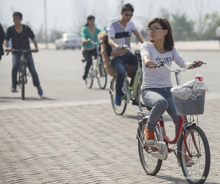 People ride on Nanbin street in Chongqing Municipality, southwest China, March 7, 2013. The highest temperature rose to 28 degrees Celsius in Chongqing on Thursday. (Xinhua/Chen Cheng)