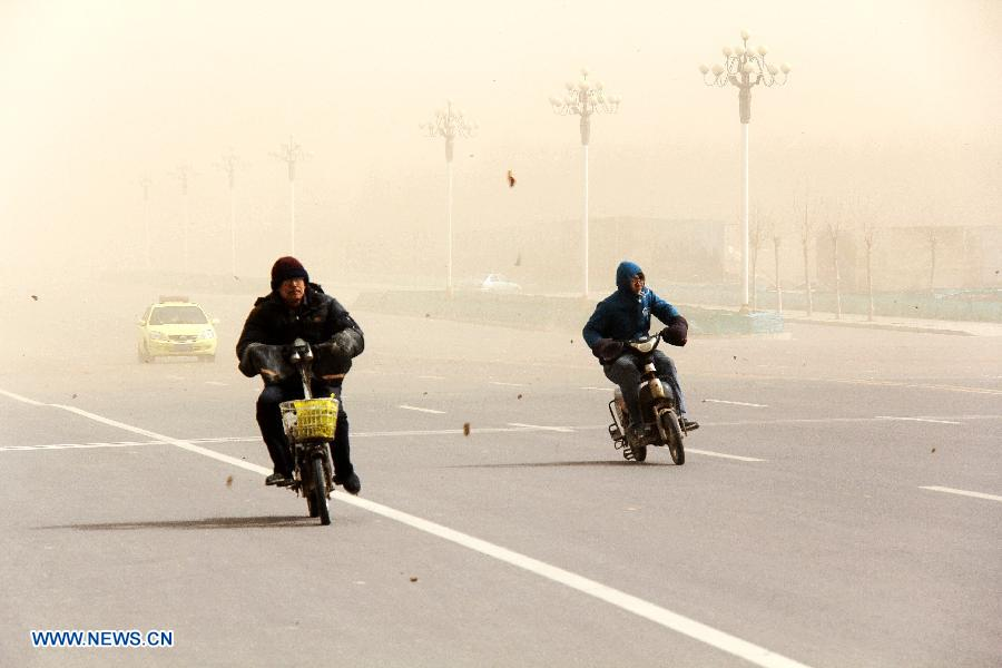 Bikers brave wind and sand on a road in Bazhou, north China's Hebei Province, March 9, 2013. A cold front brought strong wind as well as sand and dust to most part of north China region on March 9. (Xinhua/He Huaqiao)