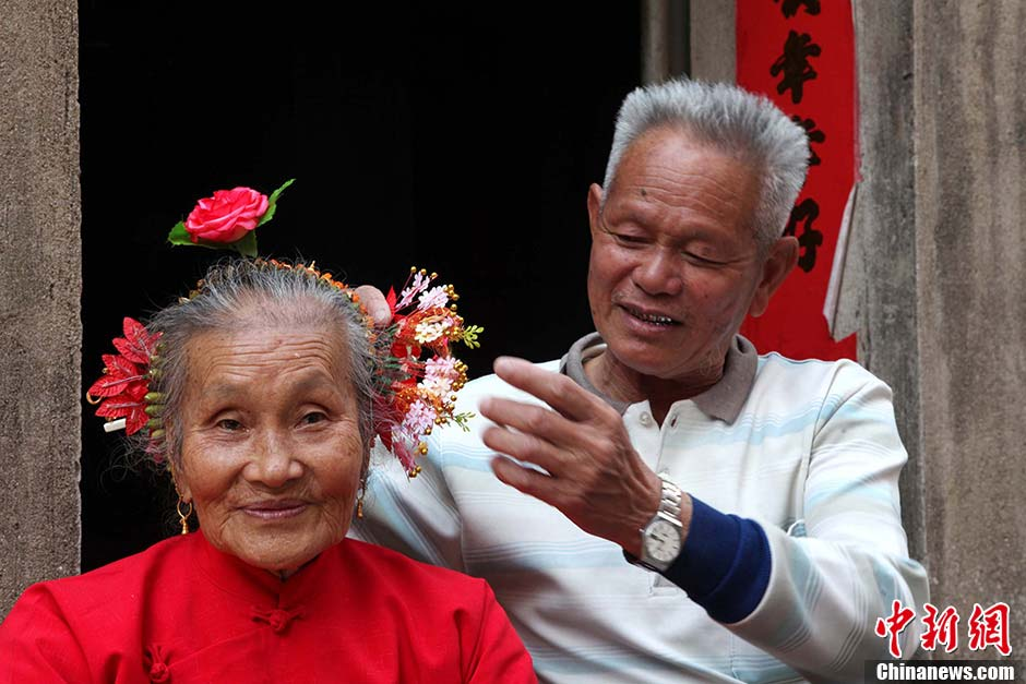 Zheng Xiya, 78, helps his wife put flowers in her hair, to celebrate the folk festival honoring the sea goddess Mazu in Xunpu village, Hui'an city of East China's Fujian province, March 10, 2013. (Photo/CNS)