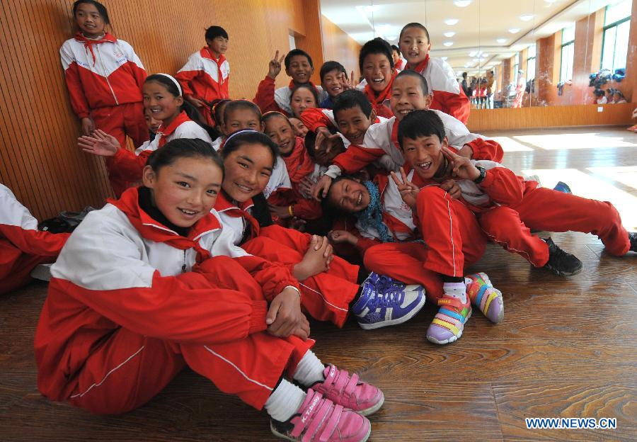 Pupils of the Tibetan ethnic group pose for photos at No. 1 Primary School of Deqin County in Diqing Tibetan Autonomous Prefecture, southwest China's Yunnan Province, March 12, 2013. A total of 1,260 pupils, most of whom are of the Tibetan ethnic group, study at this school, which was founded in September 2012. Pupils here are offered free meals and lodging. (Xinhua/Lin Yiguang)
