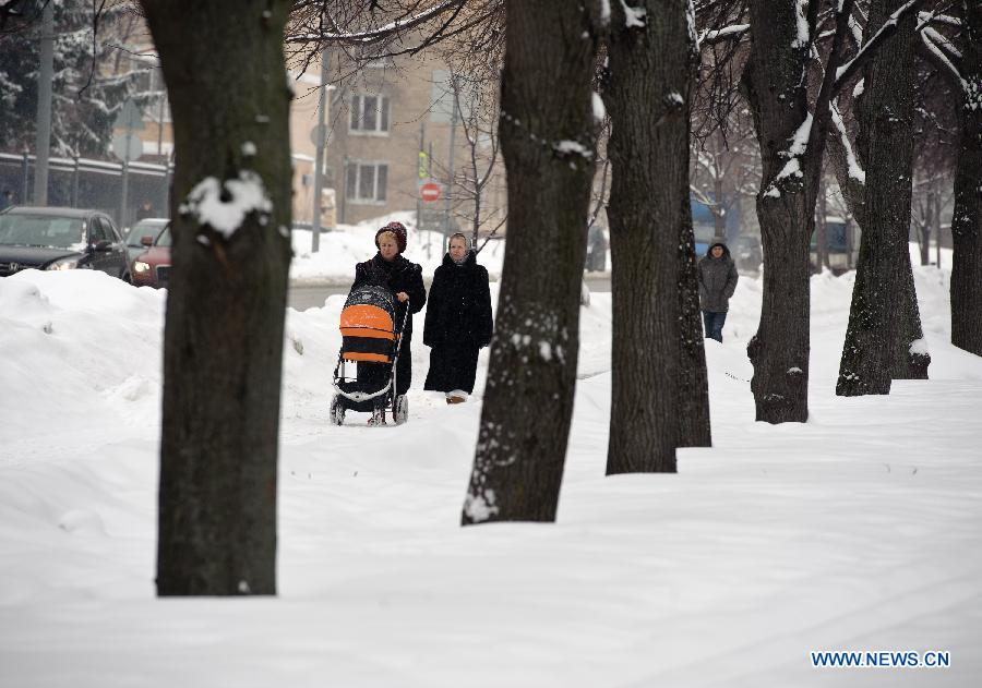 People walk during a snowfall in Moscow, Russia, March 14, 2013. A rare heavy snowfall hit Moscow on Wednesday and Thursday, causing traffic jams and disturbing scheduled flights. (Xinhua/Jiang Kehong)