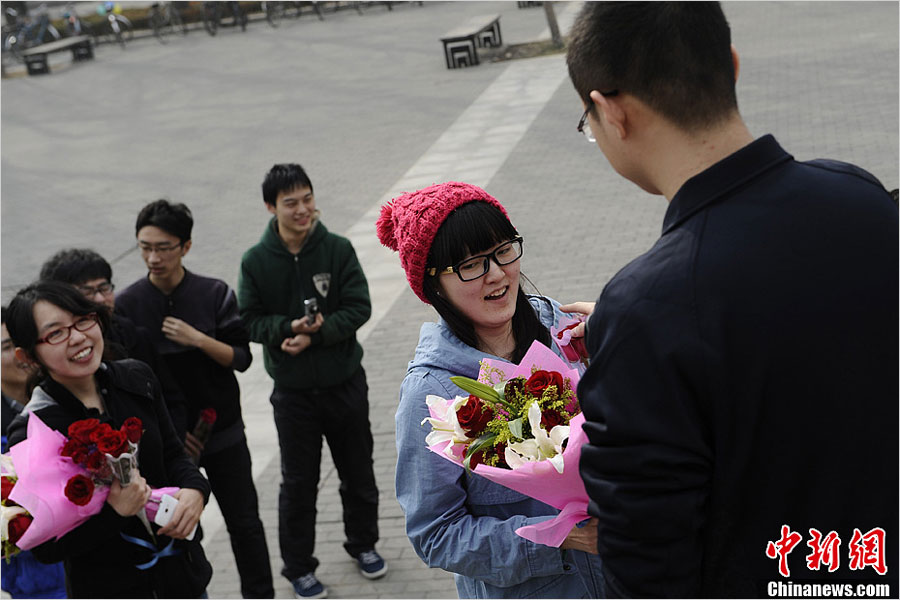 "A Tsinghua University student sends flowers to his classmate to celebrate ""Ladies' Day"" on March 7, one day before ""Women's Day"" on March 8, 2013. Data issued by China's National Bureau of Statistics indicates that there will be 24 million more unmarried men than women by the end of 2020. (news.china.com.cn)"