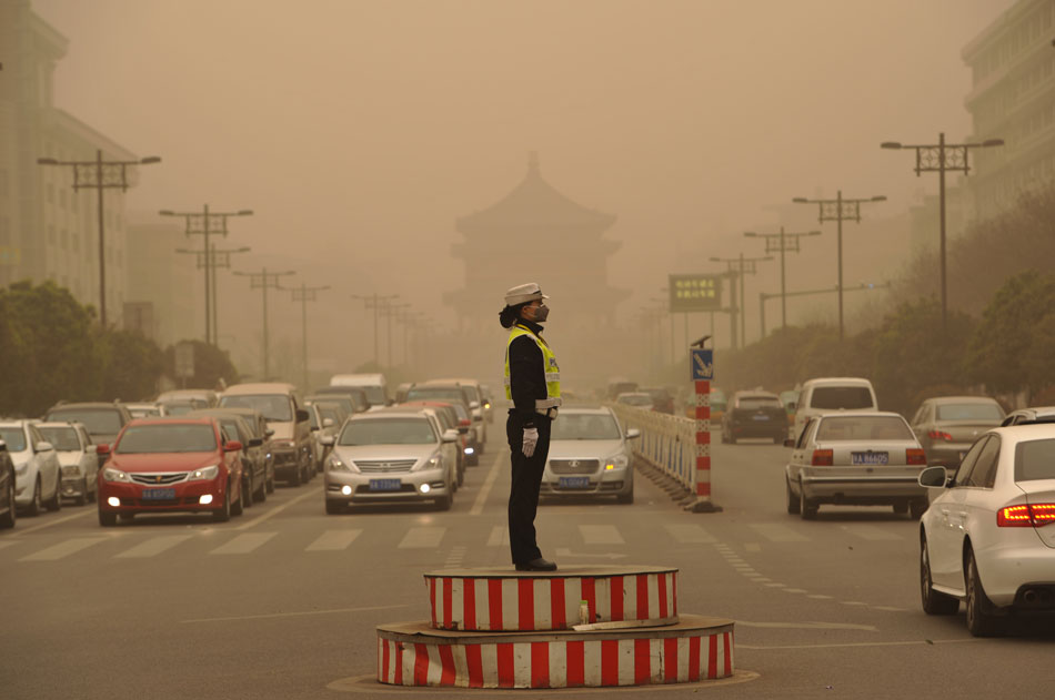 A mask-wearing female police officer directs the traffic in heavy sand and dust blown by a new round of cold front, Xi'an, northwest China's Shaanxi province,  March 9, 2013. (Xinhua/Ding Haitao)