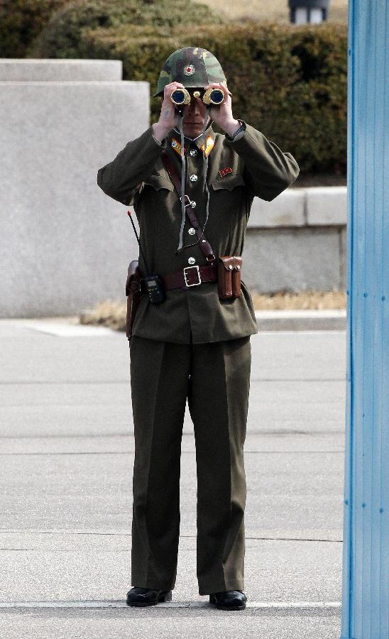 A soldier of the Democratic People's Republic of Korea (DPRK) stands guard at the truce village of Panmunjom in the demilitarized zone (DMZ) in Paju, South Korea, March 19, 2013. The annual joint military exercises of South Korea and the United States is scheduled to run from March 11 to March 21. (Xinhua/Park Jin-hee)