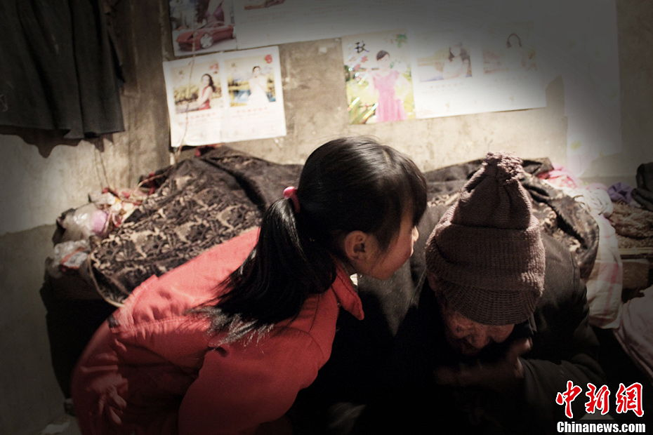 Song talks to her grandfather to his ear because he is slightly deaf. (Chinanews.com / Zhou Panpan)
