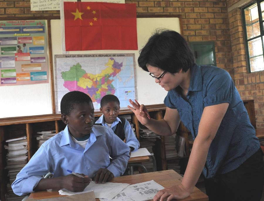 Shaodan, a Chinese teacher of Confucius Institute, teaches Chinese at a secondary school, 40 km east of Pretoria, South Africa, Feb. 25, 2013. In recent years, Africa has witnessed a growing passion for the Chinese language and increasing requests to set up Chinese teaching institutions. To cater to this growing need, China opened the Confucius Institute at the University of Nairobi in 2005, the first of its kind in Africa. The latest figure shows that there are 31 Confucius Institutes and 5 Confucius Classrooms in Africa as of September 2012. (Xinhua/Li Qihua)