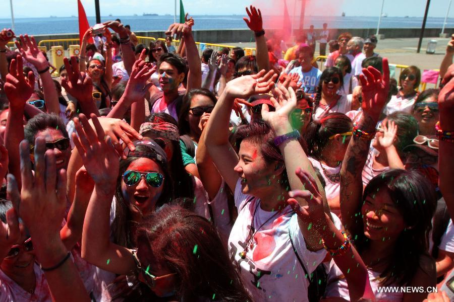 People with colored powder on their faces dance during the Holi Festival in Pasay City, the Philippines, March 24, 2013. The Holi Festival is one of the major festivals in India, celebrating the turn of the seasons from winter to spring. Also known as the Festival of Colors, it is a fun-filled celebration during which hundreds of people gather to enjoy a day of dancing, eating and throwing colored powder at one another. (Xinhua/Rouelle Umali)