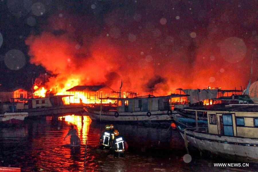 Fire fighters try to put out a fire in Kota Kinabalu, Malaysia, March 27, 2013. A fire engulfed over 400 wooden houses on the sea on Wednesday, leaving more than 3,000 people homeless and dozens injured. (Xinhua)