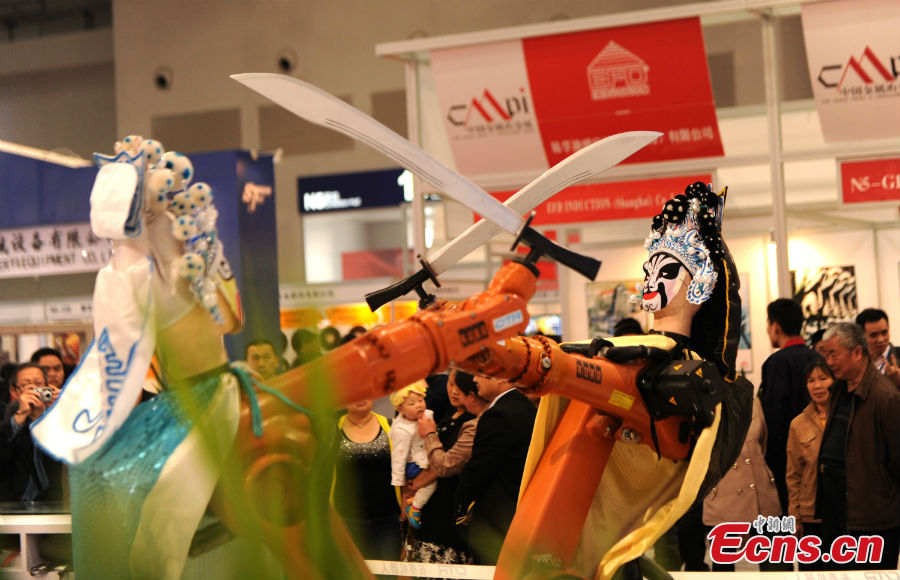Robots clad in Peking Opera costumes display their technical ability at the13th China Metal and Metallurgy Exhibition in Chongqing, March 28, 2013. (CNS/Chen Chao)
