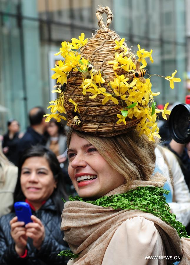 A lady with a bonnet in the shape of a hive is seen in the annual Easter Bonnet Parade in Manhattan of New York, the United States, March 31, 2013. With a history of more than 100 years, the New York Easter Bonnet Parade is held annually on the 5th Avenue near the Saint Patrick's Cathedral. Adults, children and even pets in creative colorful bonnets and outfits participate in the event, which also attract thousands of New York residents and tourists. (Xinhua/Deng Jian)