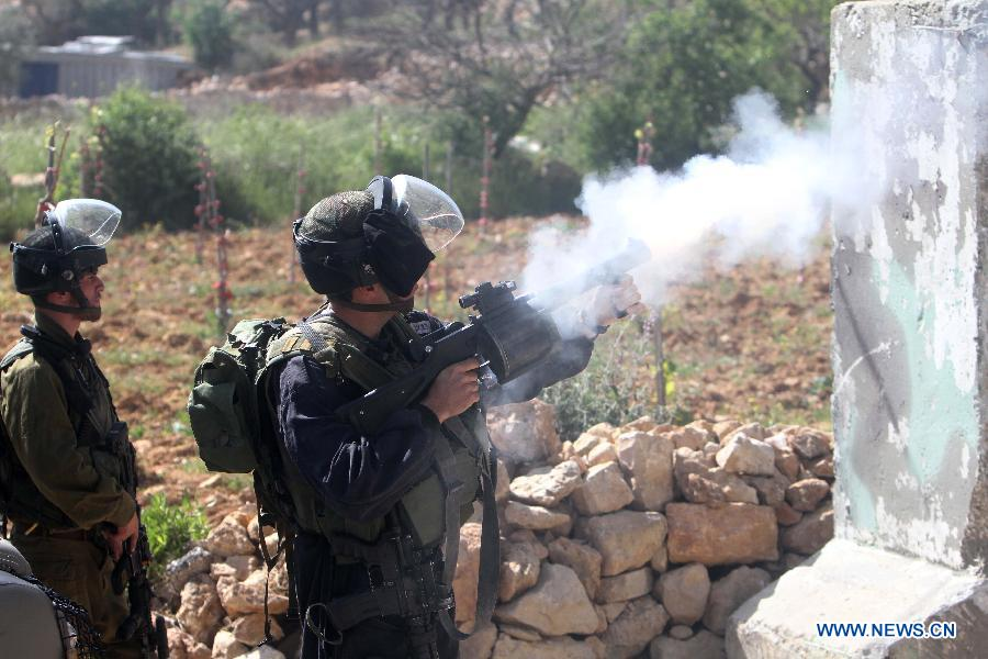 An Israeli soldier shoots tear gas toward Palestinian protesters during clashes in the West Bank village of Al-Khader near Bethlehem on March 29, 2013. (Xinhua/Luay Sababa)