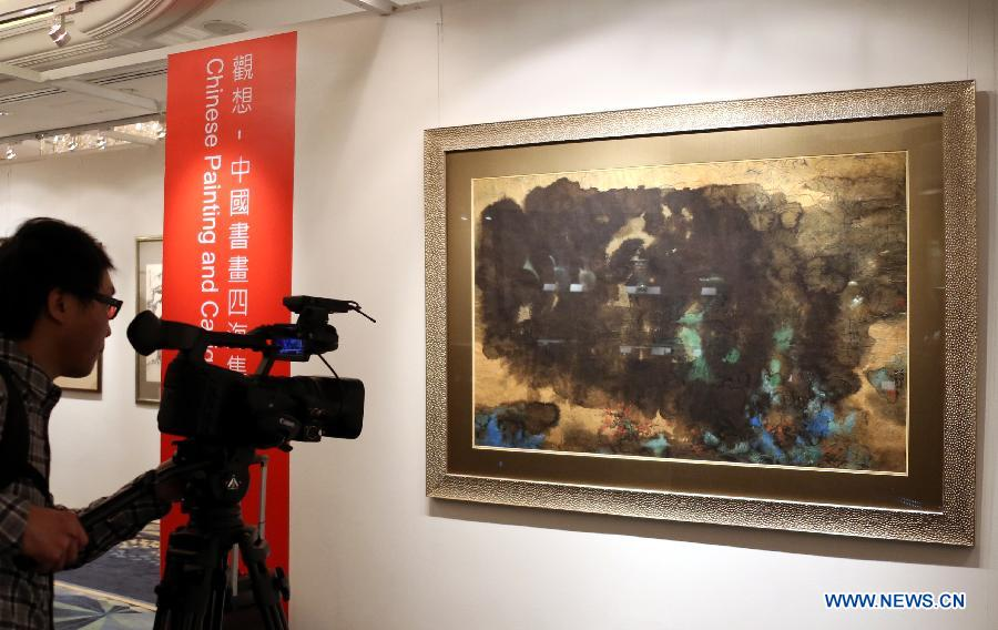 A TV journalist shoots a painting by Zhang Daqian estimated at a price of 12 million to 15 million HKD (about 1.5 million to 1.9 million U.S. dollars) during the preview of the Hong Kong 2013 Spring Auctions held by China Guardian Auctions Co.Ltd in Hong Kong, south China, April 3, 2013. The two-day auctions will start on April 4, with over 300 pieces of paintings and calligraphy as well as ceramic artworks. (Xinhua/Li Peng)