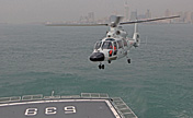 Warship in coordinated-drill with helicopter