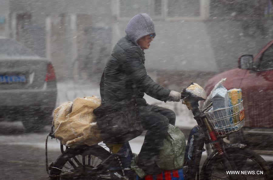 A deliveryman rides in snow in Changchun, capital of northeast China's Jilin Province, April 11, 2013. (Xinhua/Lin Hong)