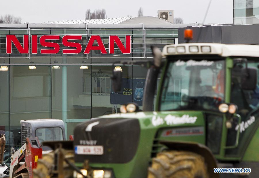 A tractor passes a sales office of Japanese auto producer Nissan in Brussels, capital of Belgium, April 11, 2013. Four Japanese auto giants (Toyota, Nissan, Honda and Mazda) said Thursday they are recalling nearly 2.92 million vehicles worldwide because of airbag problems.(Xinhua/Zhou Lei)