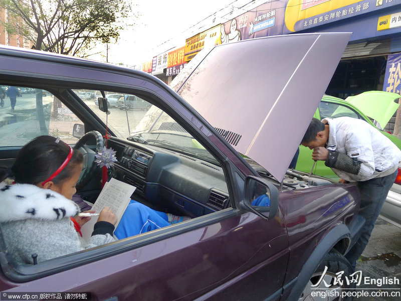 A pupil sitting in the car seizes every minute to do her homework. (Photo by Li Wenming/ CFP)