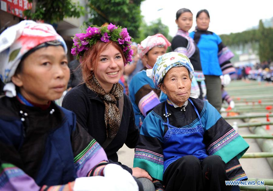 "A French woman (C, front) poses for group photos with women of Dai ethnic group during a folk custom and culture festival marking the ""San Yue San"" (the third day of the third lunar month in Chinese Calendar) in Shizong County, southwest China's Yunnan Province, April 12, 2013. The festival, attracting tens of thousands of local residents and tourists from both at home and abroad, was held here Friday. (Xinhua/Yang Zongyou)"