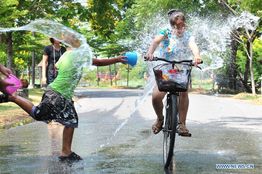 A cyclist is splashed during celebrations for Songkran Festival, Thailand's traditional New Year Festival, at the Ancient City in Samut Prakan Province, Thailand, April 14, 2013. Songkran, also known as the Water Splashing Festival, started here on April 13 this year. (Xinhua/Rachen Sageamsak)