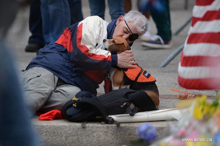A citizen kisses his dog while mourning for the victims in Boston Marathon blasts in Boston, the United States, April 16, 2013. The death toll has risen to three, with 176 people injured. (Xinhua/Wang Lei)