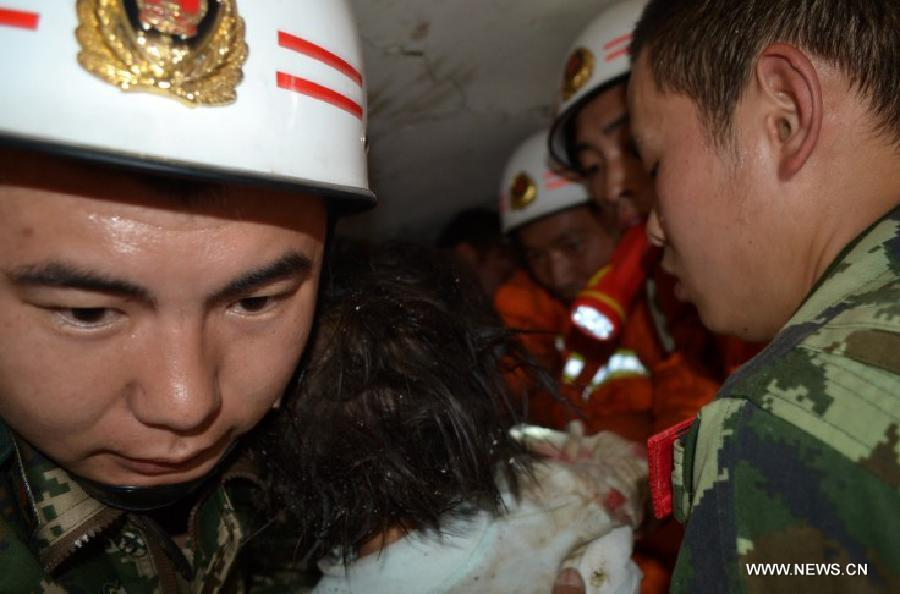 Firemen rescue a girl from debris in Lushan County of Ya'an City, southwest China's Sichuan Province, April 20, 2013. At least 113 people have been killed in the 7.0-magnitude earthquake in Sichuan Province as of 4:40 p.m. on Saturday, according to the provincial seismological bureau. (Xinhua)