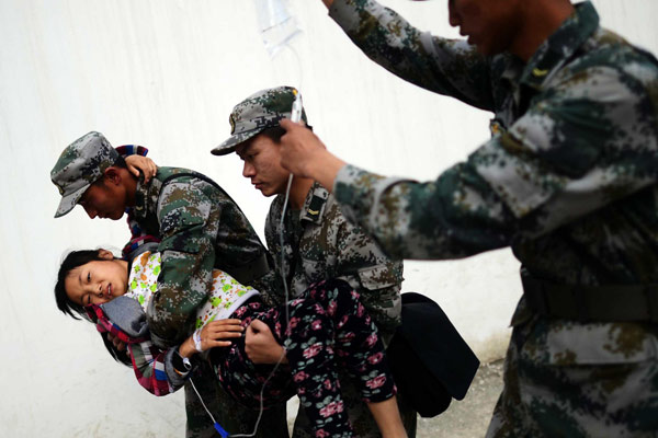 Rescue soldiers help a girl receive an infusion in Lushan county, Southwest China's Sichuan province, on April 20, 2013. A 7.0-magnitude earthquake struck the county on April 20, leaving at least 200 people dead and more than 10,000 injured. (Photo/Xinhua)
