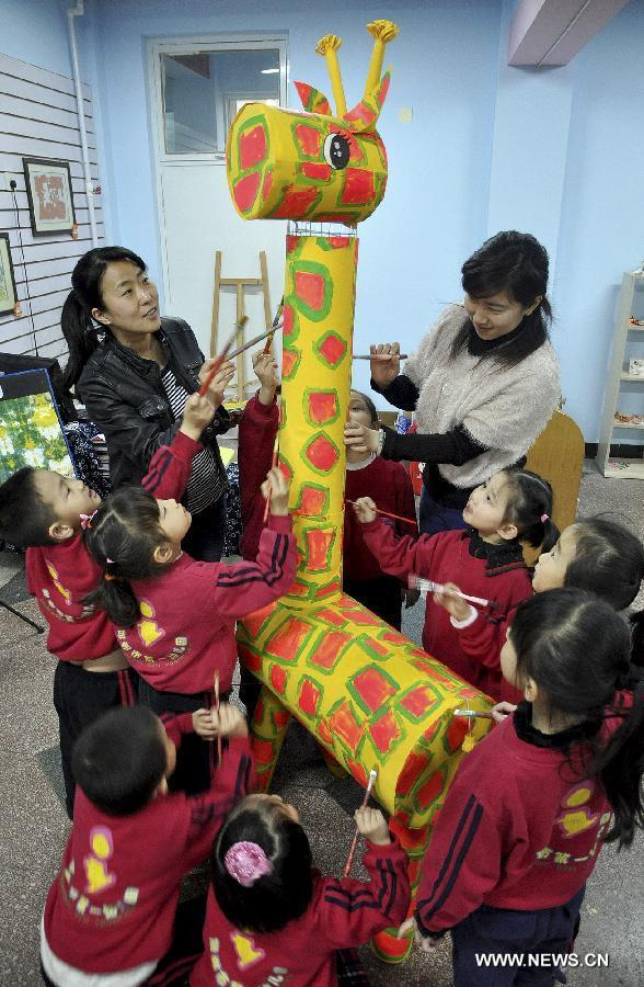 Teachers and students make a model of giraffe using waste materials during an environment protection activity in Handan, north China's Hebei Province, April 22, 2013. The environment protection activity was held to mark the World Earth Day, which falls on April 22 each year. (Xinhua/Hao Qunying)