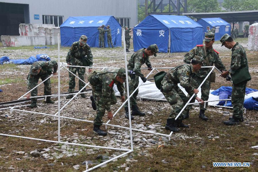 Rescuers put up tents at a temporary settlement for quake-affected people in Lingguan Township of Baoxing County, Ya'an City, southwest China's Sichuan Province, April 22, 2013. A 7.0-magnitude earthquake jolted Lushan County of Ya'an City on Saturday morning. (Xinhua/Wang Jianmin)