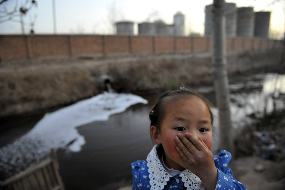 A girl covers her nose near the outfall of the Ningxia Terry Pharmaceutical Co., Ltd in Xingqing District of Yinchuan, Ningxia Hui Autonomous Region on April 1, 2013. Three big bio-fermentation pharmaceutical companies are located in the suburbs of Yinchuan. The production pollution caused serious impact on the air quality and agricultural production of the surrounding areas. People have called on the authorities to solve the pollution problems for years, but they have not been resolved. (Xinhua/Wang Peng)