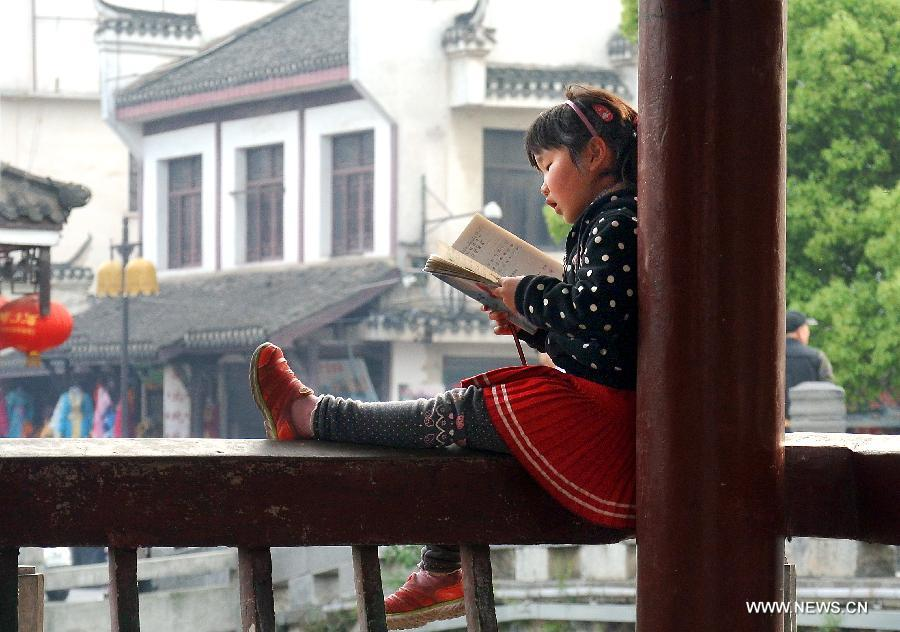 "A girl reads a book in a pavilion in Sanhe Town of Feixi County, east China's Anhui Province, April 25, 2013. The Sanhe Ancient Town, which has a history of more than 2,500 years, is a typical ""ancient town full of rivers and lakes, together with small bridges, flowing water and local dwellings."" (Xinhua/Wang Song)"