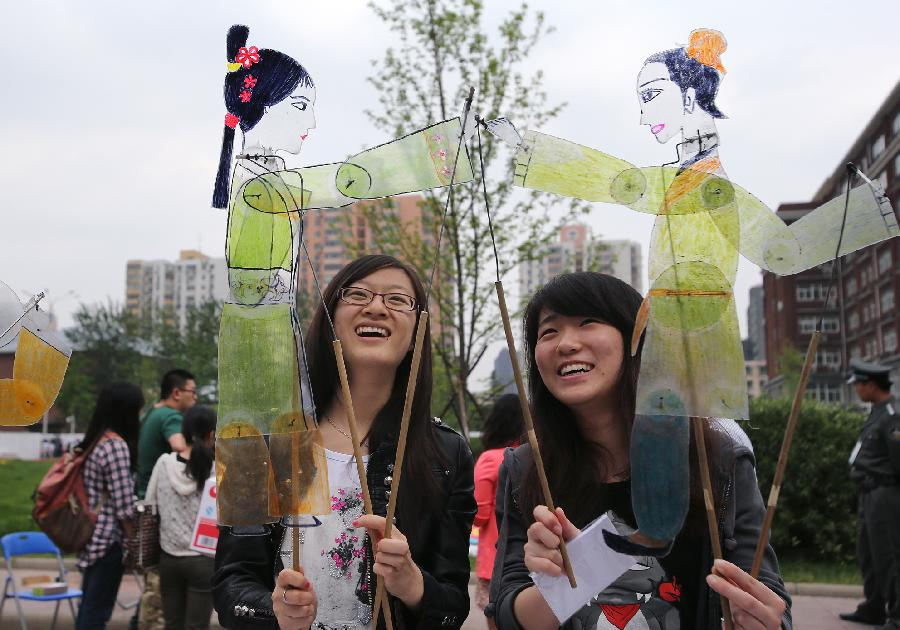 Students hold figures of traditional Chinese shadow puppet during the opening of the fourth International Cultural Festival held by the University of International Business and Economics (UIBE) in Beijing, capital of China, May 9, 2013. The cultural festival offered a stage for students from different countries to present their own culture. (Xinhua/Wan Xiang)