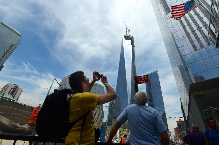 Visitors take photos of One World Trade Center (WTC) in New York, May 10, 2013. Workers have installed the final sections of the silver spire atop WTC on Friday, which brings the iconic New York City structure to its full, symbolic height of 1,776 feet (541 meters). (Xinhua/Wang Lei)
